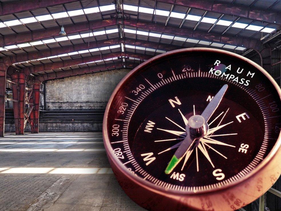 Fotocollage eines Kompasses in einer leeren Fabrikhalle