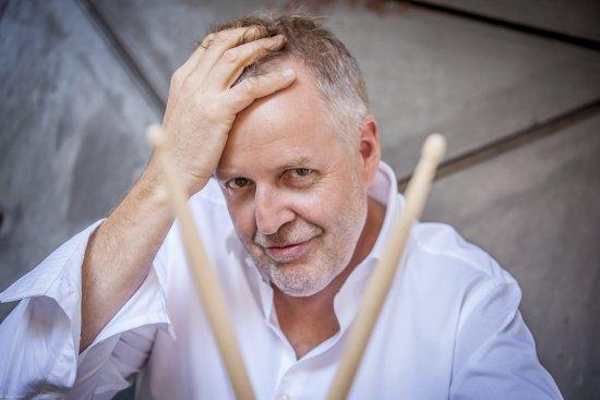 Wolfgang Haffner mit weißem Hemd schaut durch zwei gekreuzte drum sticks hindurch uns an