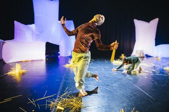 Im Vordergrund Tänzer Rouven Pabst lachend, im Hintergrund Tänzerin Juliane Bauer auf dem Boden knieend vor überdimensional großen weißen, kissenartigen Tüten