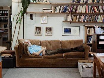 Älterer Mann liegt auf einem Sofa, das in einem Zimmer vor einer Wand mit Zimmerpflanze, Bildern und Bücherregalen steht