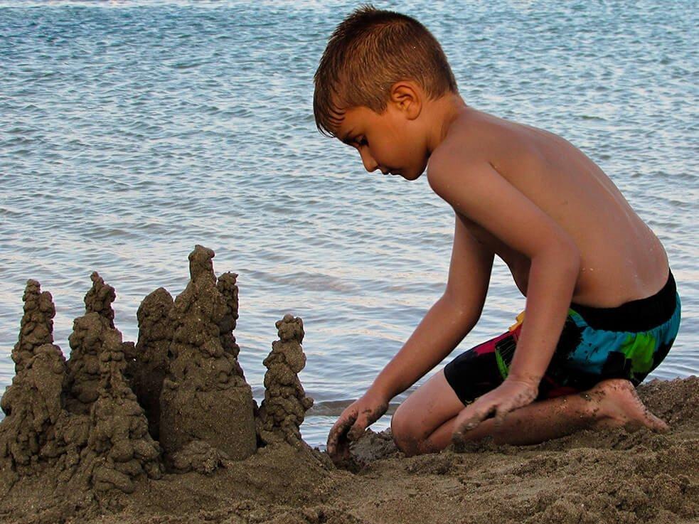 Kind baut am Strand eine Sandburg