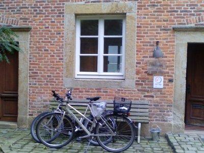 Zwei räder lehnen an einer Holzbank, vor einem Backsteinhaus