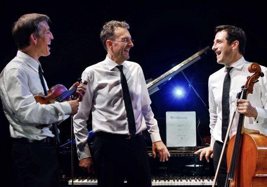 Von links nach rechts vor einem Flügel stehend und einander zulachend die Musiker Pawel Zalejski mit Violine, Stefan Danhof und  Ariel Barnes mit Violoncello