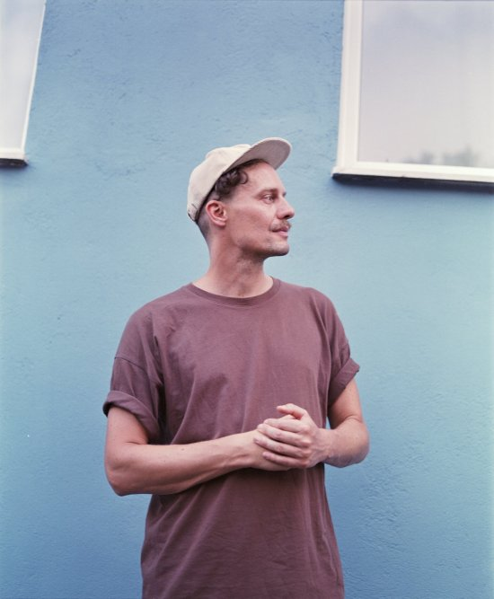 Vincent von Flieger vor einer blauen Hauswand
