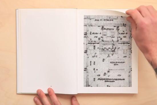eine Hand kurz vor dem Umblättern einer Buchseite