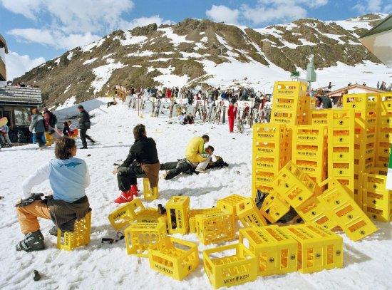 Bergstation mit Berghütte und Skifahrern. Im Bildvordergrund stehen aufgestapelte, gelbe Getränkekisten, zwei Personen sitzen auf Getränkekisten, eine Person, auf der eine zweite Person sitzt, liegt auf dem Boden im Schnee