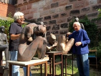 zwei Bildhauer stehen an Skulpturen