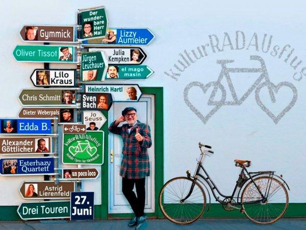 Ein Mann steht neben einem Fahrrad und lehnt sich an ein Straßenschild mit vielen Künstlernamen