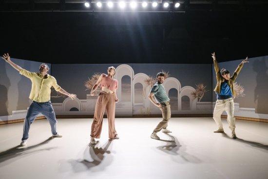 An der Bühnenkante zwei Männer und zwei Frauen in energetischen Posen, im Hintergrund Gegenlicht der Scheinwerfer,  auf der Bühnenrückwand pastellfarbiges Fotomotiv (antike Bögen und Palmen)