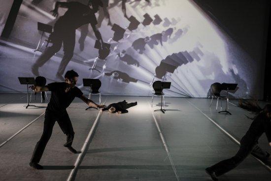 Weißer Bühnenraum, im Vordergrund Tänzer in Bewegung, im Hintergrund Tänzerin auf dem Boden liegend, vier Stühle, spiralförmig aufgefächterte Projektion des Bühnengeschehens auf Leinwand