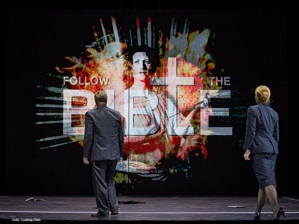"""Ein Mann und eine Frau betrachten eine Projektion mit dem Text """"Follow the bible"""""""