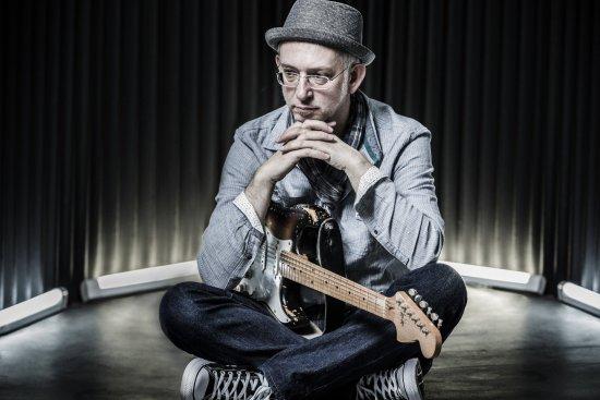 Peter Pelzner sitzend auf der Bühne mit Gitarre auf dem Schoß