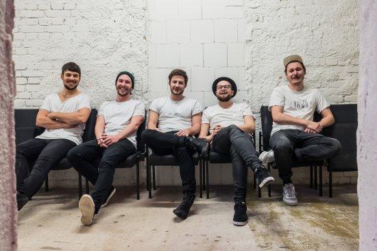 Die fünf Bandmitglieder sitzen auf schwarzen Stühlen vor einer weißen Backsteinwand.