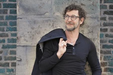 Bernd Regenauer steht vor einer Steinwand, mit einer schwarzen Jacke über der Schulter.