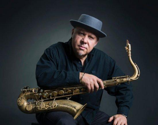 Saxofonist Tony Lakatos hält sein Instrument und schaut inspiriert in die Kamera.