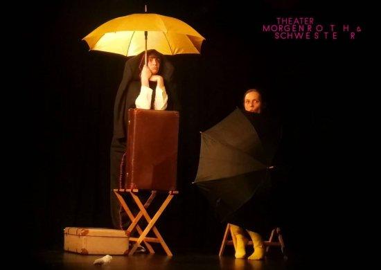 Die Schauspielerinnen Meike Hess und Rebecca Kirchmann schauen traurig unter Regenschirmen hervor.