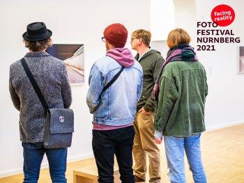 Ausstellungsbesucher beim betrachten eines Bildes in der Ausstellung