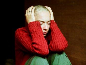 Am Boden sitzende junge Frau, die Hände auf den Kopf gelegt