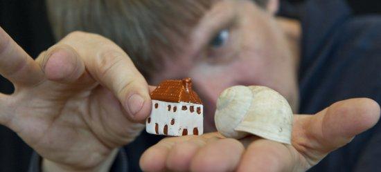 Tristan Vogt hält auf seiner flach ausgestreckten Hand eine Schneckenhaus, stellt mit anderer Hand ein kleines Häuschen in derselben Größe daneben