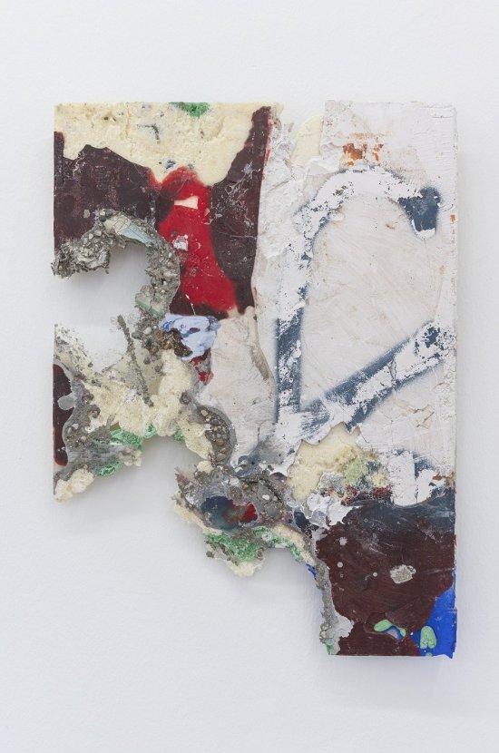 Die Abbildung zeigt eine rechteckige Arbeitsfläche, auf der verschiedenfarbige Werkstoffe aufgetragen sind. Teile der Arbeitsfläche fehlen und wirken wie herausgebrochen. Das Kunstwerk erscheint wie ein abstraktes Gemälde.