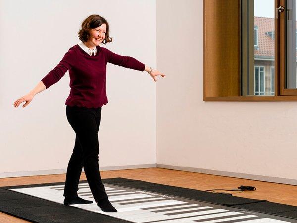Eine Frau läuft über ein Bodenklavier