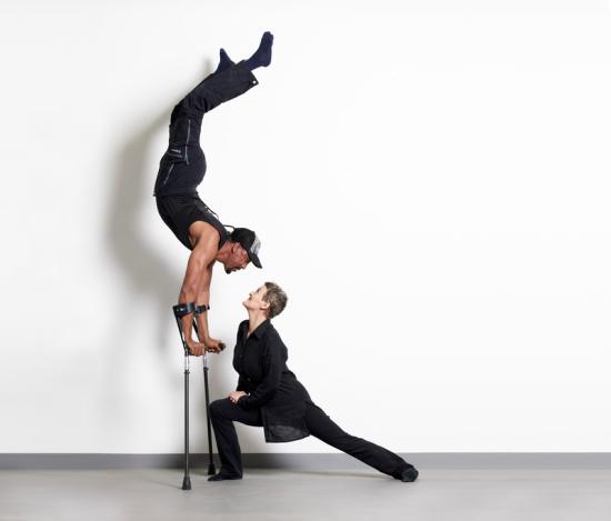 Susanna Curtis und Tameru Zegeye tanzen miteinander. Tameru Zegeye macht einen Handstand auf seinen Krücken.