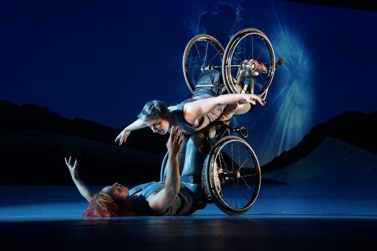 Die Tänzerin Laurel Lawson fliegt mit ihren ausgestreckten Armen durch die Luft. Sie wird von der Tänzerin Alice Sheppard gestützt, die sich von unten hochhebt. Sie schauen einander an und lächeln. Beide sitzen in einem Rollstuhl.
