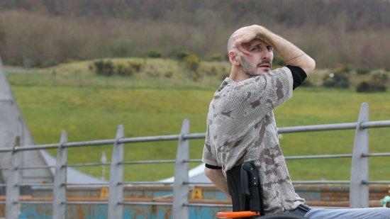Der Künstler Marc Brew sitzt an einem Zaun vor einer grünen Wiese und schaut in die Kamera.