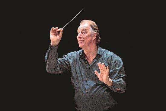 Simon van Boxtel dirigiert vor schwarzem Hintergrund