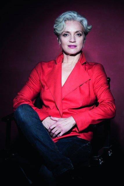 Adeline Schebecsch mit rotem Blazer vor weinrotem HIntergrund