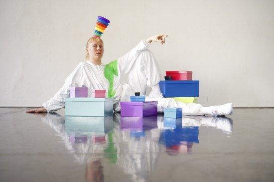Tänzerin in weißem Overall liegt hinter bunten Kartons. Die rechte Hand ist auf dem Boden aufgestützt