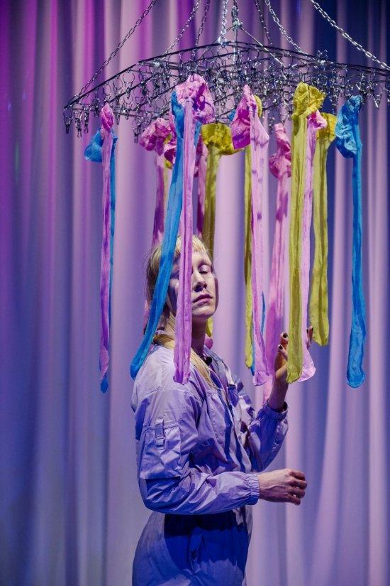 Kopf mit blonden Haaren; vor ihm hängen blaue und pinkfarbene Bänder