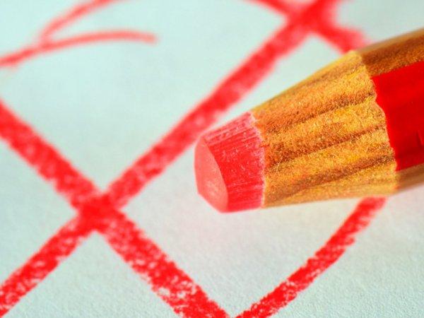 Roter Bleistift mit Wahlkreuz