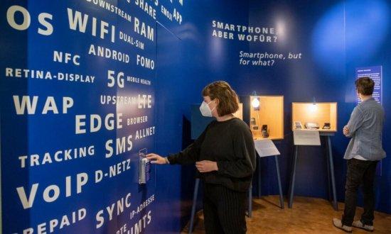 Blick in den neuen Ausstellungsbereich: Eine Frau mit Maske nimmt ein Infoblatt und ein Mann mit Maske betreachtet eine Vitrine. Die Vitrine steht vor einer blauen Wand.